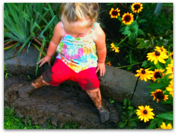 toddler playing in the mud