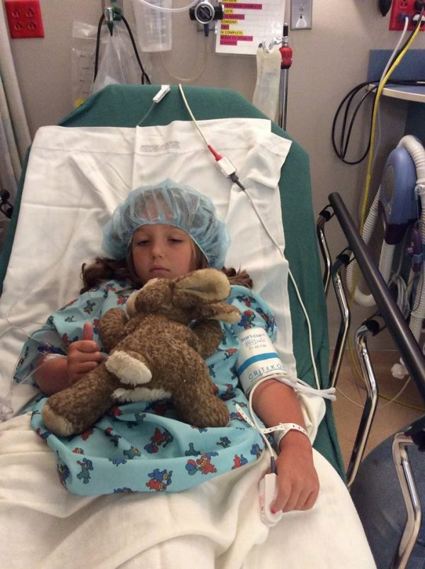 little girl in hospital bed with bunny